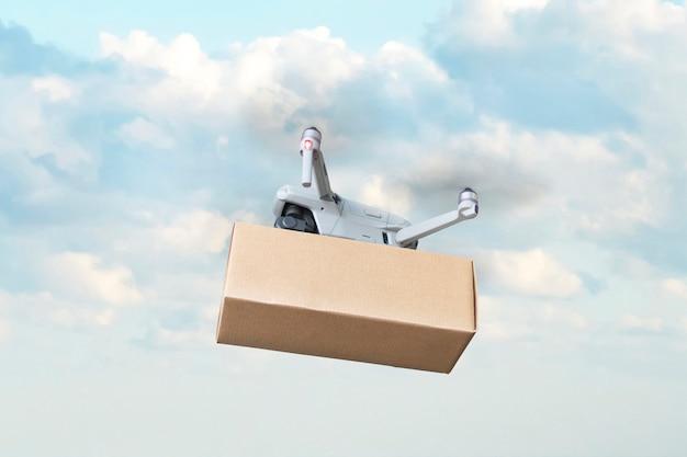 Entrega por drone contra um fundo de céu azul e nuvens brancas. entrega rápida de mercadorias por via aérea. drone com caixa de papelão