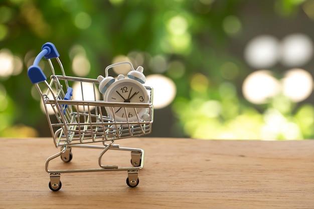Entrega rápida, conceito de valor do dinheiro no tempo: relógio analógico branco em um carrinho de compras azul - prata ou um carrinho de compras de supermercado