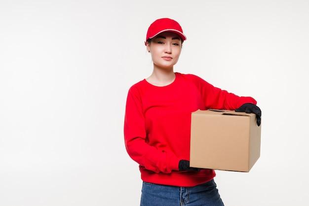 Entrega, realocação e desembalagem. mulher jovem sorridente segurando uma caixa de papelão isolada na parede branca