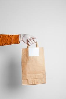 Entrega segura de alimentos em um saco de artesanato e entregador de pizza em casa, sobre um fundo branco