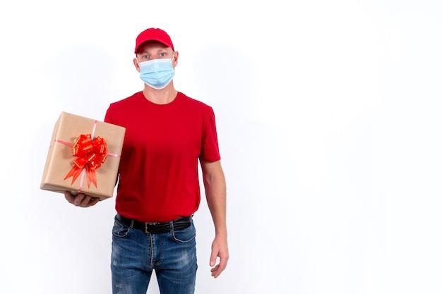Entrega segura de presentes para feriados. um mensageiro em uniforme vermelho e máscara médica segura a caixa. bandeira.
