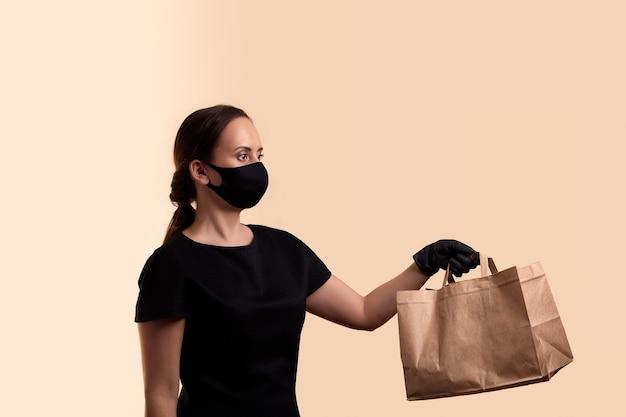 Entrega segura para mulher em quarentena com máscara facial de vestido preto e luvas de látex dá saco de papel sobre parede bege