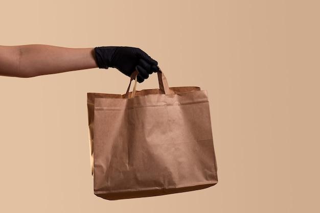 Entrega segura para quarentena feminina, mão feminina em luva de látex preta, dá saco de papel sobre parede bege
