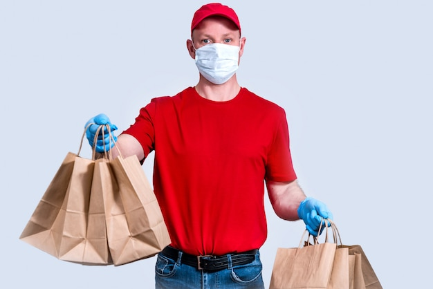 Entrega segura. um mensageiro de uniforme vermelho, máscara e luvas protetoras mantém uma grande encomenda, muitos sacos de papel, comida de entrega sem contato em quarentena. doação de voluntários. desperdício zero.