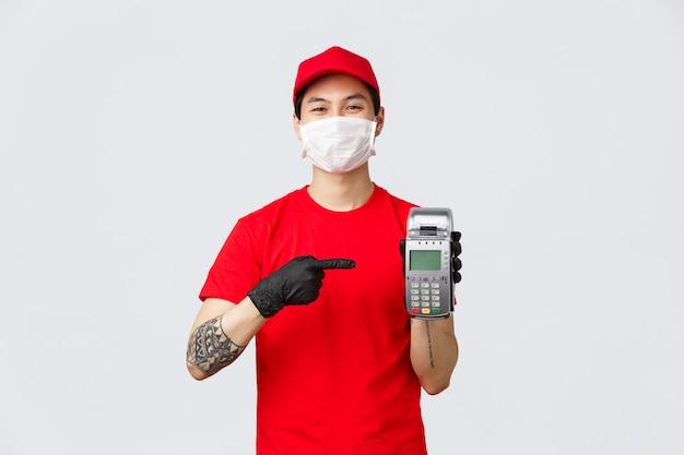 Entrega sem contato, compra segura e compras durante o conceito de coronavírus. correio asiático sorridente alegre em uniforme vermelho, máscara médica e luva, apontando para o terminal de pagamento ao cliente