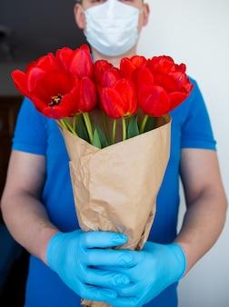 Entrega sem contato de um buquê de lindas tulipas vermelhas,
