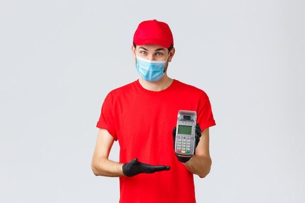Entrega sem contato, pagamento e compras online durante covid-19, quarentena automática. correio agradável com uniforme vermelho, máscara facial e luvas, solicitando o uso do terminal pos para efetuar o pagamento