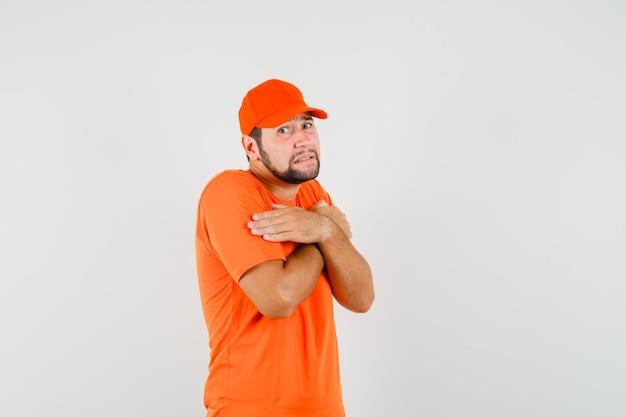 Entregador abraçando a si mesmo em t-shirt laranja, boné e parecendo humilde, vista frontal.