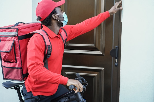 Entregador africano com bicicleta elétrica tocando a campainha na hora do coronavírus - foco no rosto