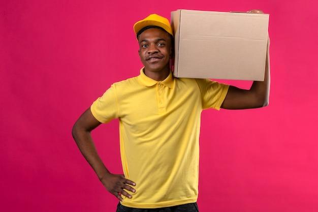 Entregador afro-americano com camisa pólo amarela e boné em pé com caixa de papelão no ombro, sorrindo amigável em rosa