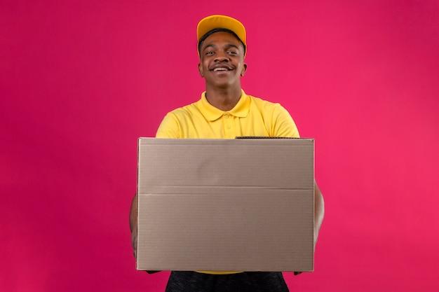 Entregador afro-americano com camisa pólo amarela e boné em pé com caixa de papelão sorrindo amigável em rosa