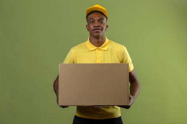 Entregador afro-americano com camisa pólo amarela e boné em pé com uma grande caixa de papelão, parecendo confiante no verde