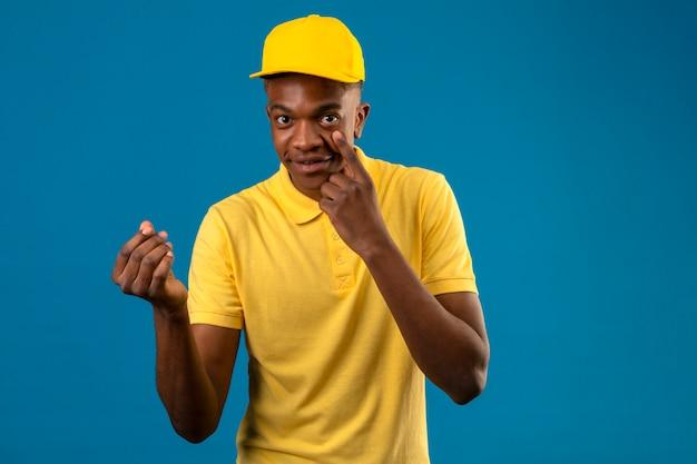Entregador afro-americano com camisa pólo amarela e boné fazendo gesto de dinheiro com a mão apontando com o dedo no olho esperando o pagamento sorrindo no isolado azul