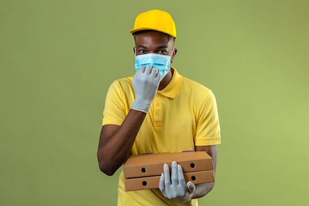 Entregador afro-americano com camisa pólo amarela e boné, máscara protetora médica, segurando caixas de pizza, parecendo animado roendo as unhas em pé no verde