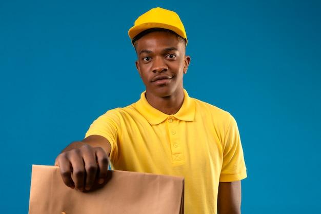 Entregador afro-americano com camisa pólo amarela e boné segurando e esticando o pacote de papel, sorrindo amigável no azul isolado