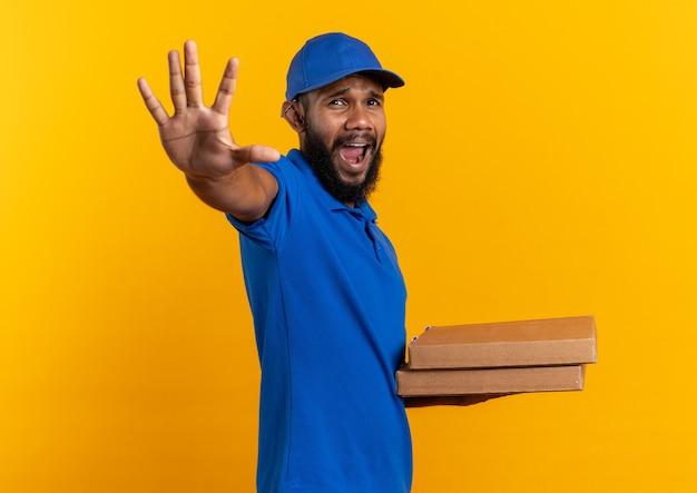 Entregador afro-americano com medo, segurando caixas de pizza e estendendo a mão, isolado na parede laranja com espaço de cópia