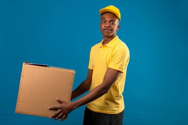 Entregador afro-americano com uma camisa pólo amarela e boné segurando caixas de papelão com um sorriso amigável em pé no azul isolado