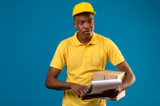 Entregador afro-americano com uma camisa pólo amarela e boné segurando uma caixa de papelão e uma prancheta concentrada na tarefa em pé no azul isolado