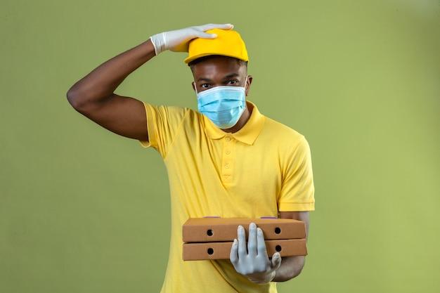 Entregador afro-americano com uma camisa pólo amarela e boné, usando máscara protetora médica, segurando caixas de pizza, parecendo ansioso e confuso com a mão na cabeça em pé no verde