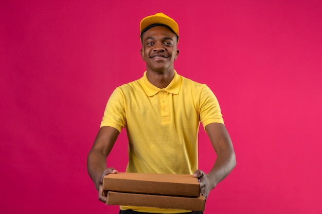 Entregador afro-americano de camisa pólo amarela e boné em pé com caixas de pizza nas mãos, estendendo-se e sorrindo amigável na rosa