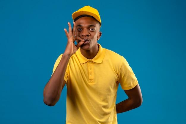 Entregador afro-americano de camisa pólo amarela e boné fazendo gesto de silêncio, como fechar a boca com zíper no azul isolado