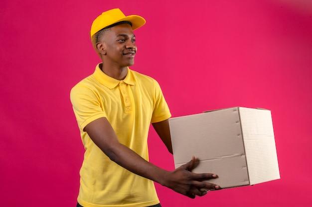 Entregador afro-americano em camisa pólo amarela e boné dando um pacote de papel para um cliente sorrindo amigável em rosa isolada