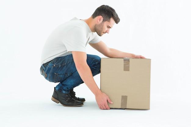 Entregador, agachando-se ao escolher a caixa de papelão