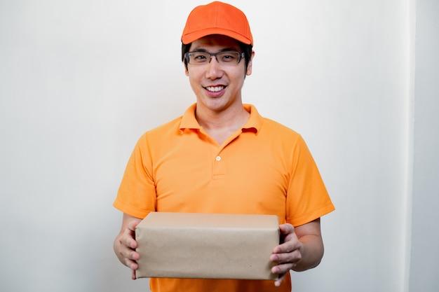 Entregador alegre com segurando a caixa de papelão.