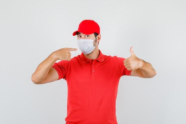 Entregador apontando para a máscara com o polegar para cima em uma camiseta vermelha
