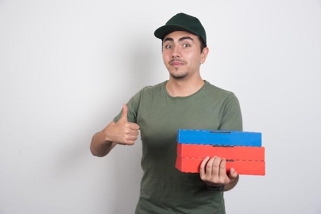 Entregador, apontando para cima e segurando caixas de pizza em fundo branco.