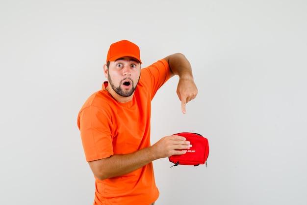 Entregador, apontando para dentro do kit de primeiros socorros em camiseta laranja, boné e parecendo ansioso, vista frontal.