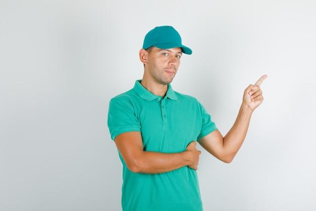 Entregador apontando para o lado em camiseta verde com boné e parecendo confiante.