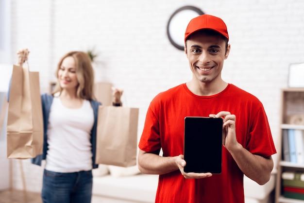 Entregador árabe com tablet e menina com packege
