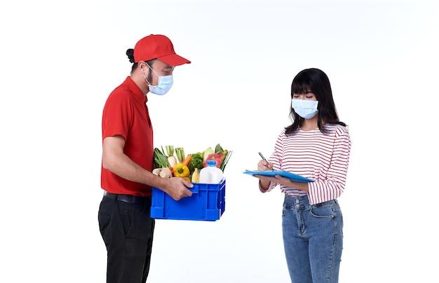 Entregador asiático com máscara facial de uniforme vermelho e caixa de mantimentos