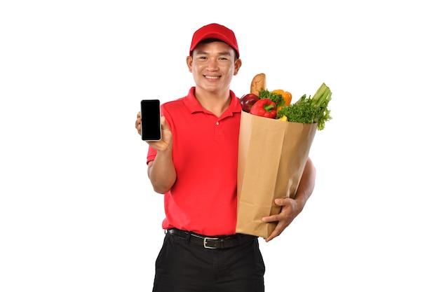 Entregador asiático com uniforme vermelho carrega uma sacola de compras e mostra o celular isolado no fundo branco