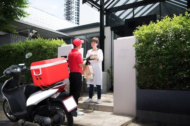 Entregador asiático de uniforme vermelho entregando sacolas de mantimentos com alimentos, frutas, vegetais e bebidas para uma mulher que está em casa