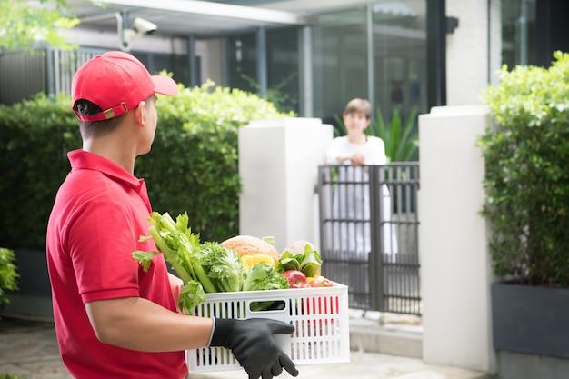 Entregador asiático de uniforme vermelho entregando uma caixa de mantimentos com alimentos, frutas, vegetais e bebidas para uma destinatária