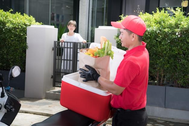 Entregador asiático de uniforme vermelho entregando uma caixa de mantimentos com alimentos, frutas, vegetais e bebidas para uma receptora em casa Foto Premium