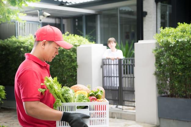 Entregador asiático de uniforme vermelho entregando uma caixa de mantimentos com alimentos, frutas, vegetais e bebidas para uma receptora em casa