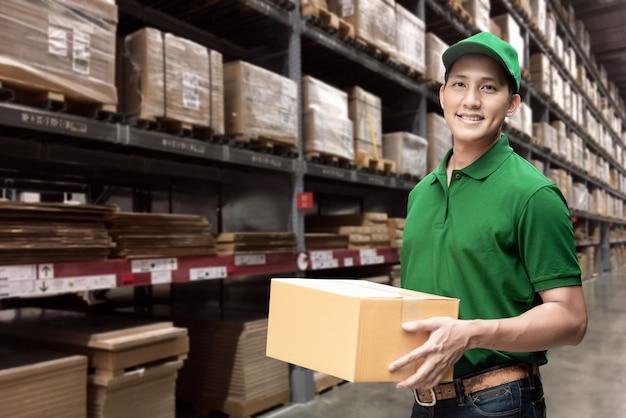 Entregador asiático ou passageiro segurando uma caixa de papelão com armazém de logística em segundo plano