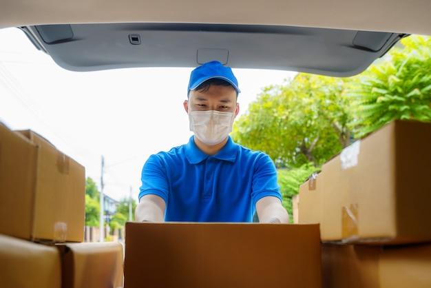 Entregador asiático presta serviço de mensageiro trabalhando com caixas de papelão em uma van