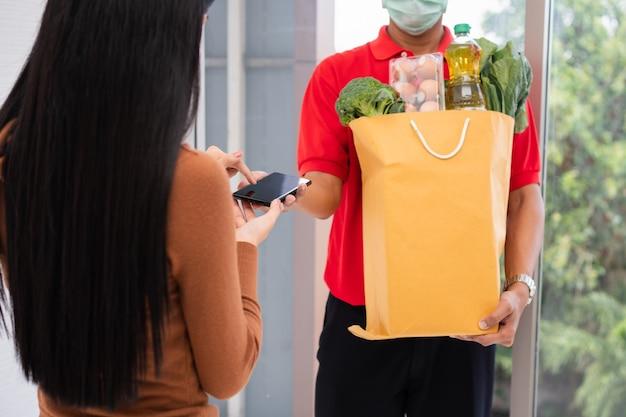 Entregador asiático segurando uma sacola de comida fresca para dar aos clientes e segurando um smartphone para receber pagamentos em casa