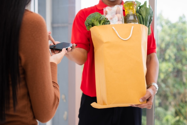 Entregador asiático segurando uma sacola de comida fresca para dar aos clientes e segurando um smartphone