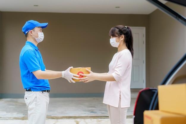 Entregador asiático usando máscara e segurando uma caixa de papelão