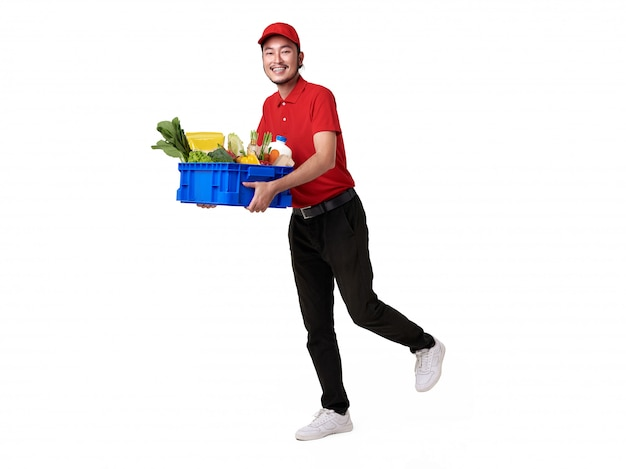 Entregador asiático vestindo uniforme vermelho, segurando uma cesta de alimentos frescos isolada no espaço em branco. serviço de entrega expressa.