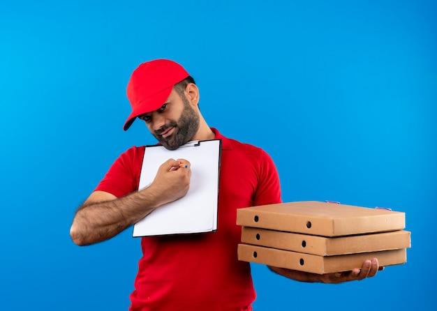 Entregador barbudo com uniforme vermelho e boné segurando caixas de pizza e prancheta com páginas em branco pedindo assinatura sorrindo em pé sobre a parede azul
