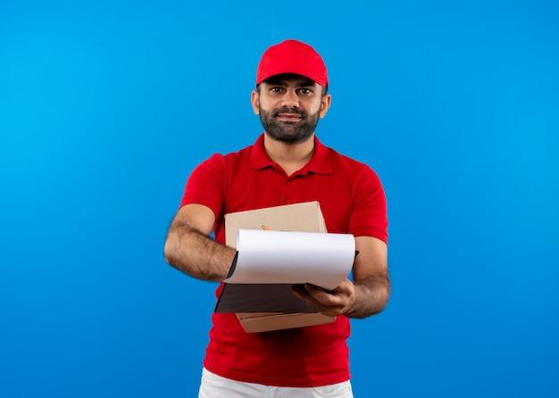 Entregador barbudo com uniforme vermelho e boné segurando o pacote da caixa e a prancheta com páginas em branco pedindo assinatura sorrindo em pé sobre a parede azul