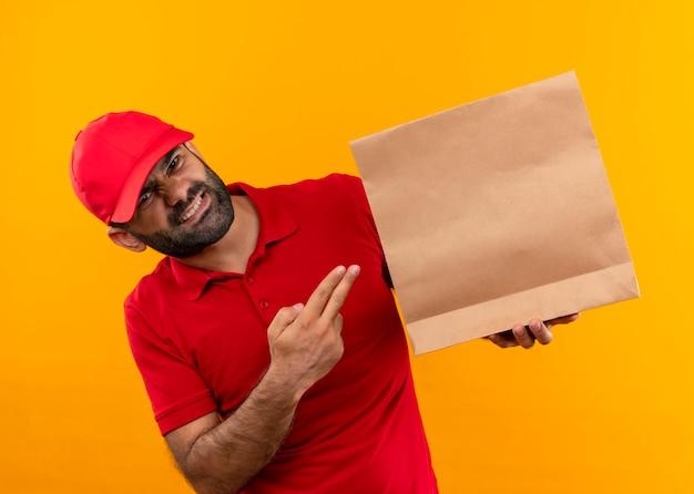 Entregador barbudo com uniforme vermelho e boné segurando um pacote de papel apontando com o dedo para ele com expressão irritada em pé sobre a parede laranja