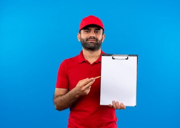 Entregador barbudo com uniforme vermelho e boné segurando uma prancheta com páginas em branco pedindo uma assinatura em pé sobre a parede azul