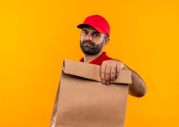 Entregador barbudo de uniforme vermelho e boné segurando um pacote de papel com rosto sério em pé sobre uma parede laranja